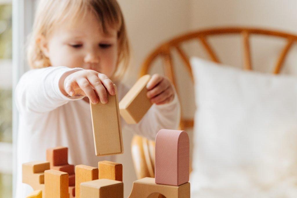 kind leert van blokken bouwen